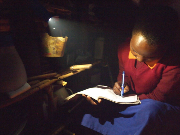 Child doing homework after dark.