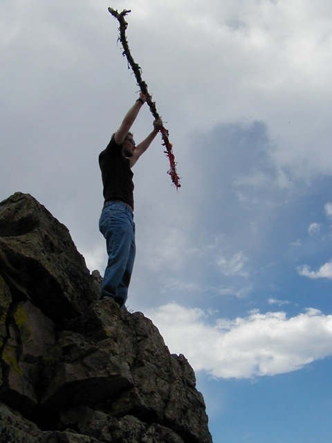 A young man stands on a rock outcrop holding up a staff to commemorate his Journey to Manhood