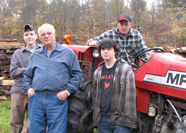 A farm family by their tractor without a roll bar